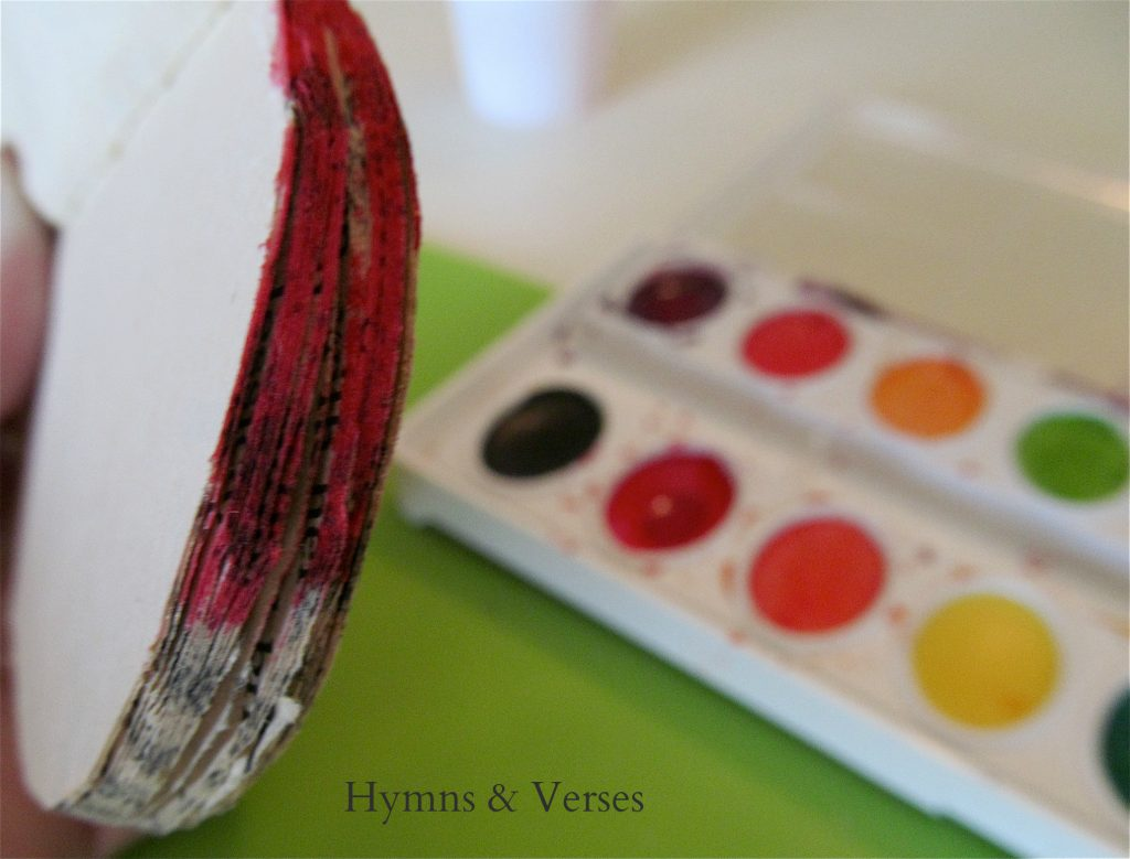How to Make a Book Page Apple - Use red watercolor paint to paint the edges of the cut apple book pages